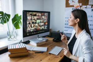 vrouw achter een mac in een digitale vergadering